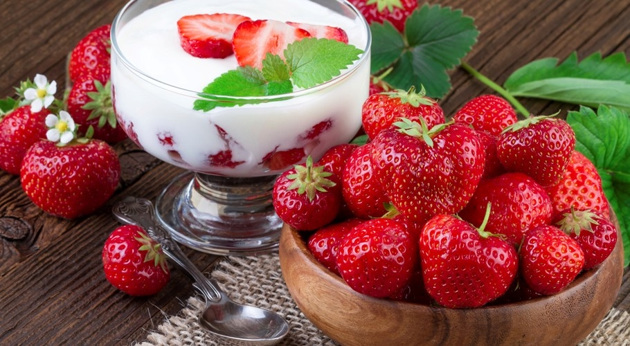 A bowl of fresh strawberries and a bowl of strawberries and cream