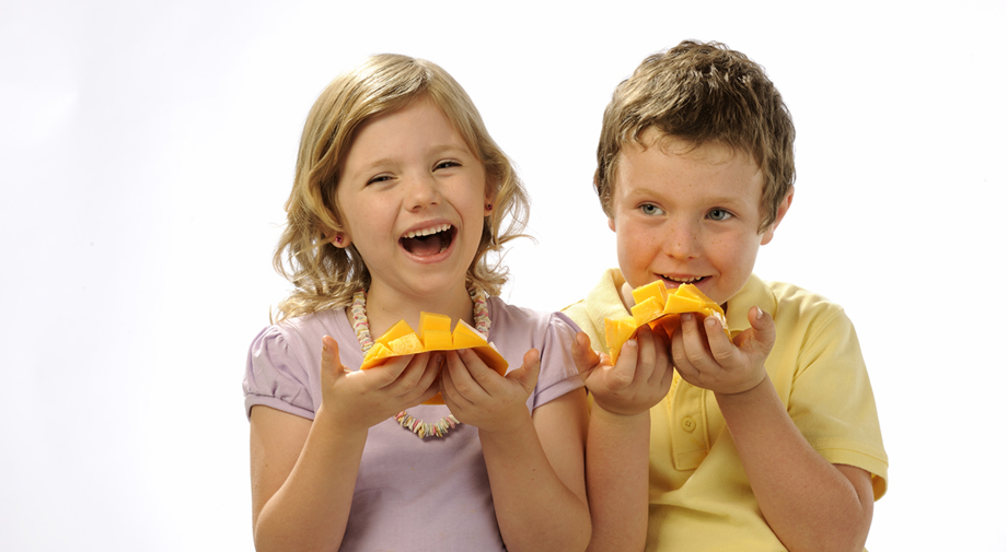 A girl and a boy eating fresh Honey Gold mangoes